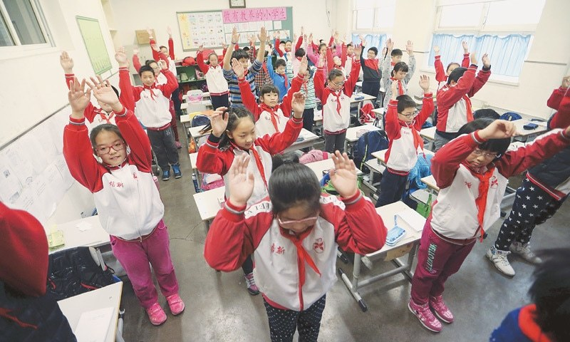 Primary school students exercise inside a classroom as outdoor activities are banned due to heavy smog. Reuters