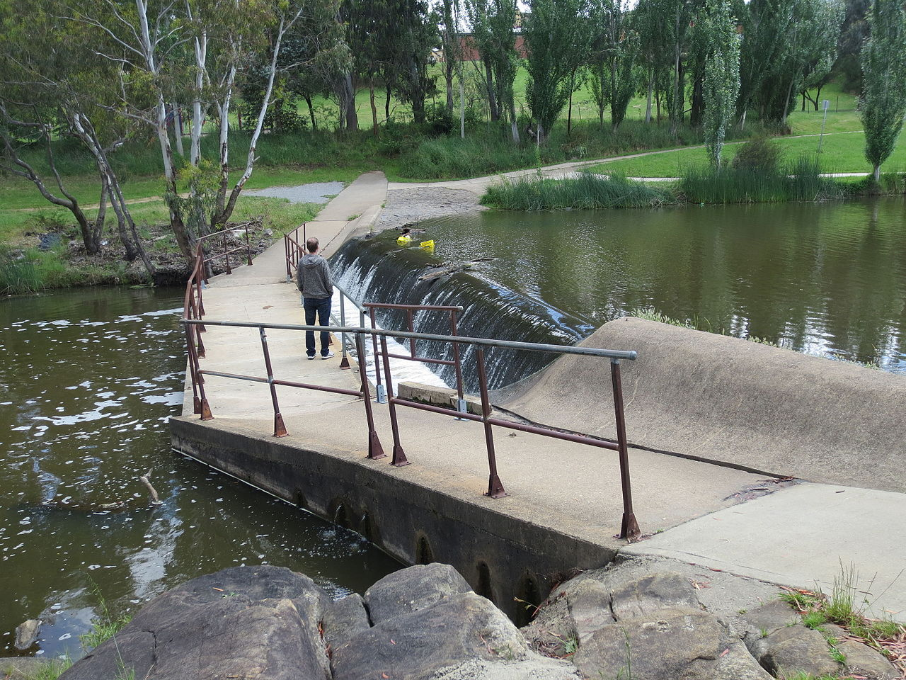 A weir on the Yass River directly upstream from a shared pedestrian/cycle river crossing (Person for scale)
