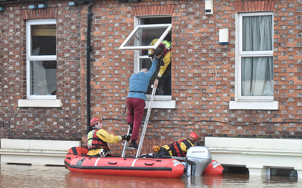 A man is helped from a first floor window by rescue teams in Carlisle, Cumbria, UK (Dec, 2015). Photo: Paul Kingston/North News