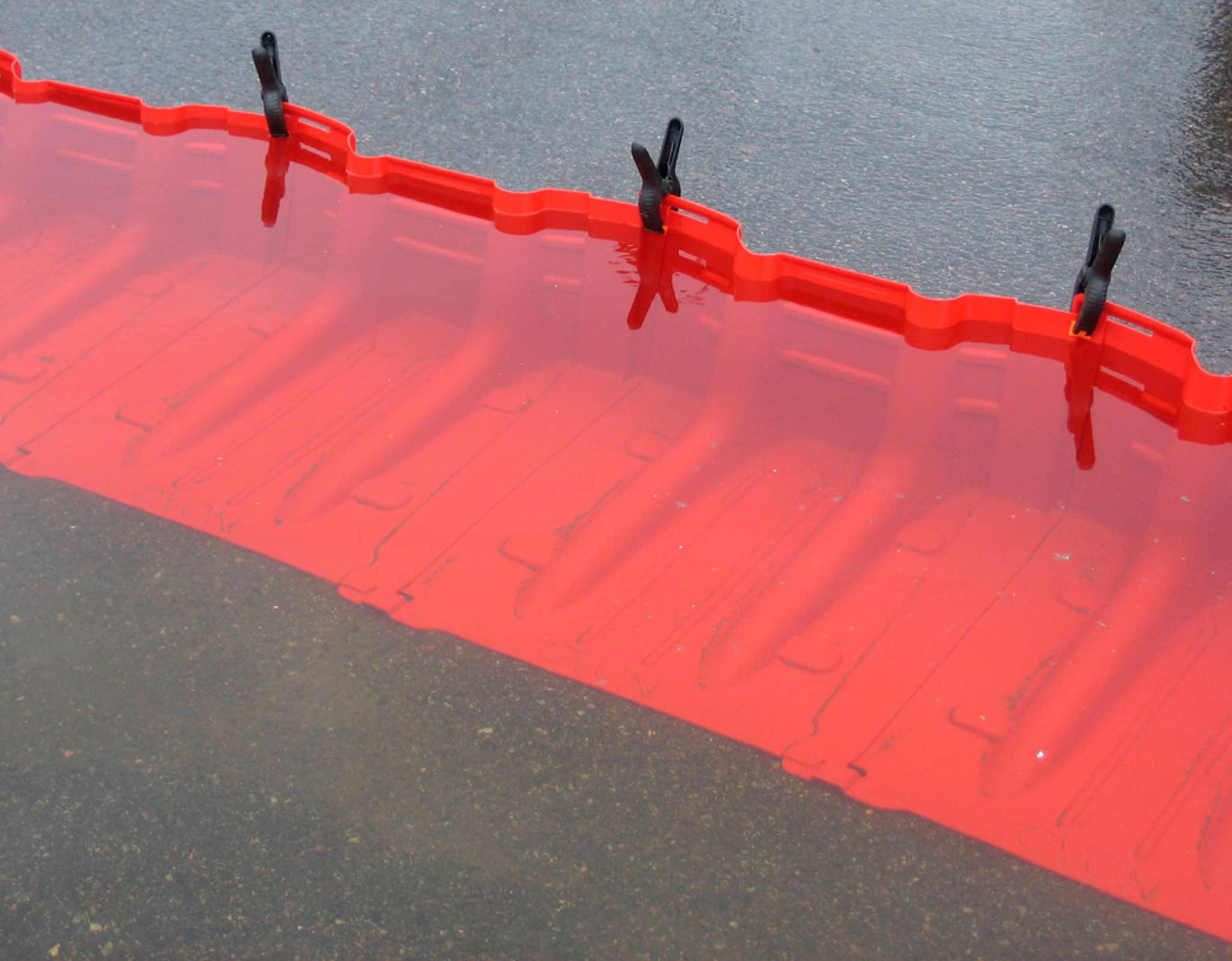 Freestanding temporary flood barrier designed for fast response to flood threats in an urban environment, on hard and even surfaces like tarmac, paving and concrete.